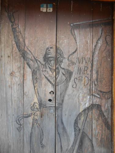 Imagen de El grafiti histórico en las calles de Morelos (propio), Estampa de Miguel Hidalgo en una puerta antigua (atribuido)