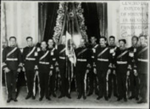 Imagen de Los Miembros del Estado Mayor Presidencial escoltan la Bandera Nacional, antes de entregarla al Presidente de la Huerta momentos antes de la ceremonia probablemente de El Grito (atribuido)