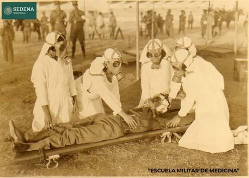 Imagen de Registro fotográfico del momento en que cuatro enfermeras con máscaras antiguas atienden a un cadete (atribuido)