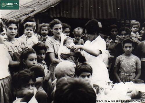 Imagen de Enfermera da de beber a un lactante mientras es sostenido por su madre (atribuido)