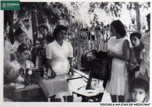 Imagen de Enfermera orienta a mujeres que cosen en máquina (atribuido)