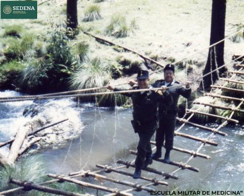 Imagen de El director de la Escuela Médico Militar, el general Enrique Espino, y un militar no identificado atraviesan un puente de troncos, como parte de los ejercicios de maniobras militares (atribuido)