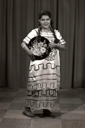 Imagen de Retrato de niña con vestido de manta bordado y charola con motivos vegetales, probablemente después de un baile escolar, en estudio (atribuido)