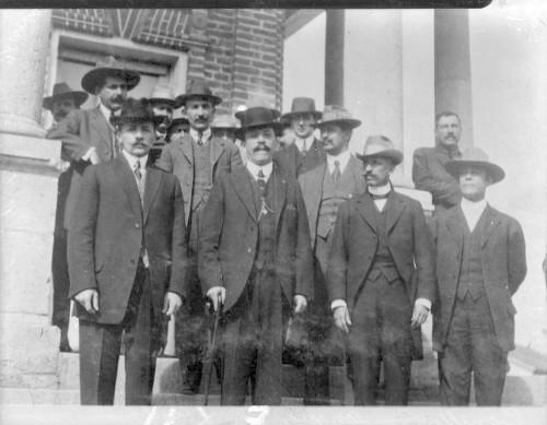 Imagen de Felipe Ángeles y otros revolucionarios fuera de un edifico, retrato de grupo